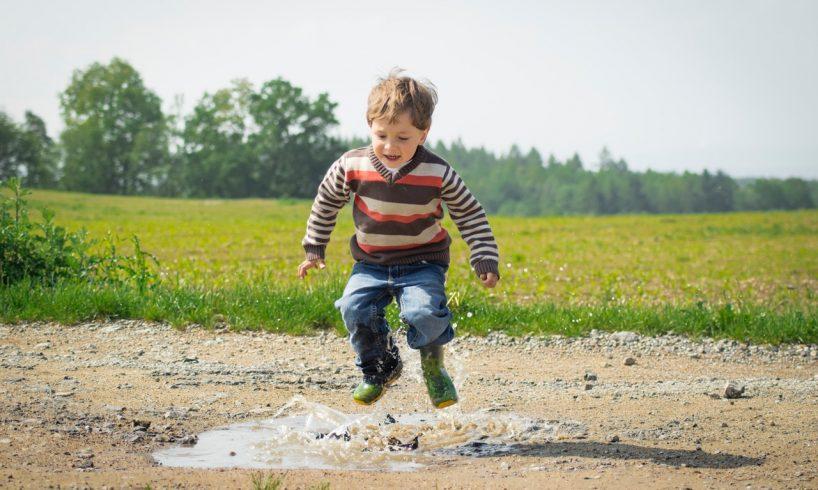 Barn hopper i vandpyt