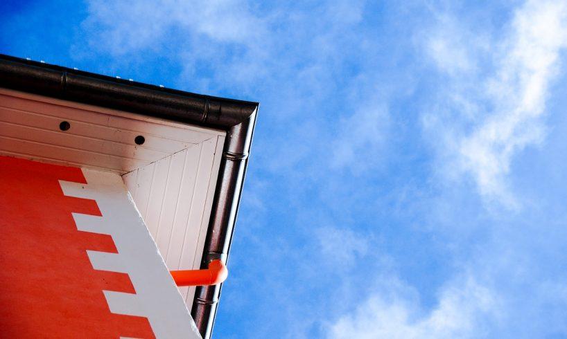 Tagrender på orange bygning med blå himmel